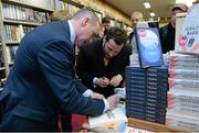 12 November 2014; Former Republic of Ireland international Alan McLoughlin, left, signs the book of Patrick Carroll, right, from Templeogue, Dublin, at the launch of  'A Different Shade of Green. Dubray Bookshop, Grafton Street, Dublin. Picture credit: Barry Cregg / SPORTSFILE