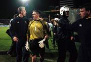 17 November 1999; Republic of Ireland manager Mick McCarthy and goalkeeper Dean Kiely leave the pitch helped by riot police after the UEFA European Championships Qualifier Play-Off Second Leg match between Turkey and Republic of Ireland at Ataturk Stadium in Bursa, Turkey. Photo by Brendan Moran/Sportsfile