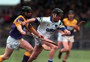 27 February 2000; Dave Bennett of Waterford is tackled by Sean Flood of Wexford during the Church & General National Hurling League Division 1B Round 2 match between Waterford and Wexford at Walsh Park in Waterford. Photo by Matt Browne/Sportsfile