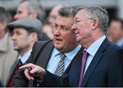 12 March 2015; Former Manchester United manager Sir Alex Ferguson, right, and trainer Paul Nicholls watch their horse Rainy City compete in The St Patricks Day Derby. Cheltenham Racing Festival 2015, Prestbury Park, Cheltenham, England. Picture credit: Ramsey Cardy / SPORTSFILE