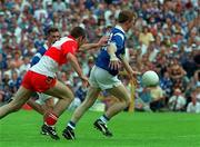 Jason Reilly  scores the winning goal for Cavan despite the attentions of David O'Neill Derry , ( Ulster Football Championship Final, Clones, 20/7/97. )  Photograph David Maher SPORTSFILE.