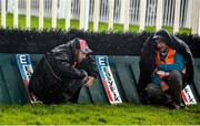 28 July 2015; Track personnel huddle near a jump to stay dry in the midst of a rain shower. Galway Racing Festival, Ballybrit, Galway. Picture credit: Cody Glenn / SPORTSFILE