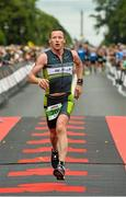 9 August 2015; Dessie Duffy, Ireland, during today's inaugural IRONMAN 70.3 Dublin. Dublin City Council hosted the competition which saw over 2500 athletes complete a 1.2 mile swim in Scotsman's Bay in Dun Laoghaire, before mounting their bikes to travel through Dublin and west of the city for a 56 mile cycle, to return to the Phoenix Park for the 13.1 mile half-marathon.    1,500 Irish athletes took part in today's event and 1,000 international athletes from 40 countries travelled to Dublin to compete in the gruelling competition. Chesterfield Avenue, Phoenix Park, Dublin. Picture credit: David Maher / SPORTSFILE