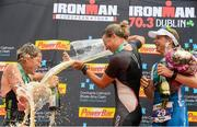 9 August 2015; Susie Cheetham, centre, Great Britain, celebrates with second place Samantha Warriner, left, New Zealand, and third place Sonja Tajisich, Germany, after fighting off stiff competition to take the gold medal at today's inaugural IRONMAN 70.3 Dublin. Dublin City Council hosted the competition which saw over 2500 athletes complete a 1.2 mile swim in Scotsman's Bay in Dun Laoghaire, before mounting their bikes to travel through Dublin and west of the city for a 56 mile cycle, to return to the Phoenix Park for the 13.1 mile half-marathon.    1,500 Irish athletes took part in today's event and 1,000 international athletes from 40 countries travelled to Dublin to compete in the gruelling competition. Chesterfield Avenue, Phoenix Park, Dublin. Picture credit: David Maher / SPORTSFILE