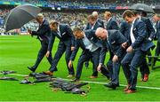 20 September 2015; Members of the Cork 1990 Jubilee Football team race to collect their umbrellas after sitting for a team photograph during their presentation to the crowd before the game. GAA Football All-Ireland Senior Championship Final, Dublin v Kerry, Croke Park, Dublin. Picture credit: Piaras Ó Mídheach / SPORTSFILE
