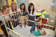 28 September 2015; Joshua McDonald, 9 months old, from Limerick City, Co. Limerick, with Cork ladies footballers, from left, Aisling Hutchings, Rois'n Phelan, Ciara O'Sullivan and Aisling Barrett during a visit by the TG4 Ladies Football All-Ireland Senior Champions to Temple Street Hospital, Temple Street, Dublin. Picture credit: Sam Barnes / SPORTSFILE