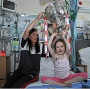 28 September 2015; Isabel O'Dwyer, from Dublin, with Cork ladies footballer Ciara O'Sullivan during a visit by the TG4 Ladies Football All-Ireland Senior Champions to Temple Street Hospital, Temple Street, Dublin. Picture credit: Sam Barnes / SPORTSFILE