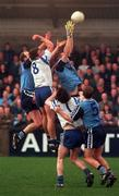 Dublin's Ciaran Whelan (yellow gloves) and Brian Stynes go up for a ball with Monaghan's Pauric McShane as Mark Daly (Mon) and Keith Barr (D. no 5) await the dropping ball  during their NFL game at Parnell Park. 15/2/98. Photograph: Brendan Moran SPORTSFILE.