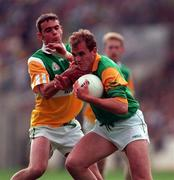 24 May1998. Meath's John McDermott brushes off the tackle of Offaly's James Grennan. Meath v Offaly, Leinster Football Championship, Croke Park. Picture Credit Ray McManus/SPORTSFILE