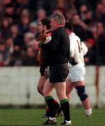 Linesman PJ Quinn takes the dog off the field at half-time during the Down v Kildare National League game in Newry. 14/12/97. Photograph David Maher SPORTSFILE.