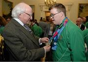 25 November 2015; Sean Coleman, a member of Cork Special Olympics Swimming Club, from Youghal, Co. Cork, has his medals admired by President Michael D. Higgins in Aras an Uachtarain as the Special Olympics World Summer Games are honoured by President Michael D. Higgins. Aras an Uachtarain, Phoenix Park, Dublin. Picture credit: Cody Glenn / SPORTSFILE