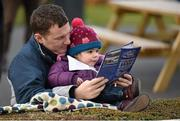 28 February 2016; Lucy Codd, age 2, from Goatstown, Co. Dublin, studies the race card with her father Joe Codd around the parade ring. Leopardstown, Co. Dublin. Picture credit: Cody Glenn / SPORTSFILE