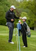 18 May 2016; Shane Lowry, left, signs the hat of Eoin Scanlon, age 11, from Clara, Co. Offaly, during the Dubai Duty Free Irish Open Golf Championship Pro-Am at The K Club in Straffan, Co. Kildare. Photo by Diarmuid Greene/Sportsfile