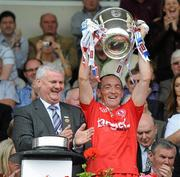 18 July 2010; Tyrone Captain Brian Dooher lifts the Anglo Celt cup, after receiving it from Ulster GAA President Aogan Farrell. Ulster GAA Football Senior Championship Final, Monaghan v Tyrone, St Tighearnach's Park, Clones, Co. Monaghan. Picture credit: Oliver McVeigh / SPORTSFILE