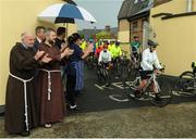 24 June 2016; 100 cyclists set off on their 2 day journey from the Capuchin Day Centre in Smithfield to Belmullet, Co. Mayo. The cyclists, among them Mayo legend David Brady, are closing in on their fundraising target of €100,000 which will go directly to the Capuchin Day Centre which has been providing relief for the homeless since 1969. Pictured is Brother Kevin Crowley, far left, as he applauds cyclsits as they leave on their journey. Capuchin Day Centre, Smithfield, Dublin. Photo by Seb Daly/Sportsfile