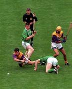 1 Septmber 1996; Wexford pair Adrian Fenlon, left, and George O'Connor in action against Limerick pair Mike Houlihan, (standing), and Sean O'Neill, as referee Pat Horan looks on, Wexford v Limerick, All Ireland Hurling Final, Croke Park, Dublin. Picture credit; David Maher / SPORTSFILE