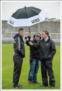 "6 March 2016; We've got you covered. TG4 floor manager Odhrán Mac Murchadha shields Kerry hurling manager Ciarán Carey from the elements as Micheál Ó Domhnaill conducts a pre-match interview  Picture credit: Brendan Moran / SPORTSFILE  This image may be reproduced free of charge when used in conjunction with a review of the book ""A Season of Sundays 2016"". All other usage © SPORTSFILE"