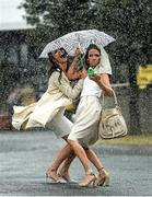 6 April 2016; Michelle Courtney, left, from Mullingar, Co. Westmeath, and Jane Boland from Portmarnock, Co. Dublin, make their way into the racecourse during a heavy shower. Leopardstown, Co. Dublin. Photo by Paul Mohan/Sportsfile
