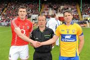 22 May 2011; Team captains Graham Canty, Cork, and Gordon Kelly, Clare, right, shake hands in front of referee Eddie Kinsella before the game. Munster GAA Football Senior Championship Quarter-Final, Cork v Clare, Pairc Ui Chaoimh, Cork. Picture credit: Pat Murphy / SPORTSFILE