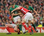 5 February 2012; Jamie Heaslip, Ireland, with support from Donncha O'Callaghan is tackled by Wales players Rhys Gill and Rhys Priestland, right. RBS Six Nations Rugby Championship, Ireland v Wales, Aviva Stadium, Lansdowne Road, Dublin. Picture credit: Stephen McCarthy / SPORTSFILE