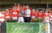 18 June 2017; Uachtarán Chumann Lúthchleas Aogán Ó Fearghail  presents Cian Byrne captain of Feathar-St Mogues, Co Wexford with the trophy after the Division 5 Final between Feathar-St Mogues, Co Wexford and Horsewood, Co. Wexford at the John West Féile na nGael national competition which took place this weekend across Carlow, Kilkenny and Waterford. This is the second year that the Féile na nGael and Féile Peile na nÓg have been sponsored by John West, one of the world's leading suppliers of fish. The competition gives up-and-coming GAA superstars the chance to participate and play in their respective Féile tournament, at a level which suits their age, skills and strengths. Photo by Matt Browne/Sportsfile