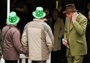 14 March 2012; A couple wearing plastic shamrock hats in attendance during Ladies Day at the Cheltenham Festival. Cheltenham Racing Festival, Prestbury Park, Cheltenham, England. Picture credit: Brendan Moran / SPORTSFILE