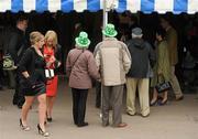 14 March 2012; A couple wearing plastic shamrock hats in attendance during Ladies Day at the Cheltenham Festival. Cheltenham Racing Festival, Prestbury Park, Cheltenham, England. Picture credit: Brendan Moran / SPORTSFILE