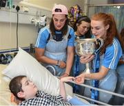 25 September 2017; Ryan Lally, age 10, from Tumhe, Co Galway, meets Dublin Senior Ladies Footballers Denise McKenna, left, and Lauren Magee, with the Brendan Martin Cup, during the All-Ireland Senior Ladies Football Champions visit to Temple Street Children's Hospital at Temple Street Children's Hospital, in Dublin. Photo by Cody Glenn/Sportsfile